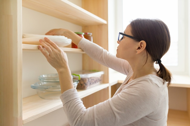 Adult woman picking food from storage cabinet in kitchen