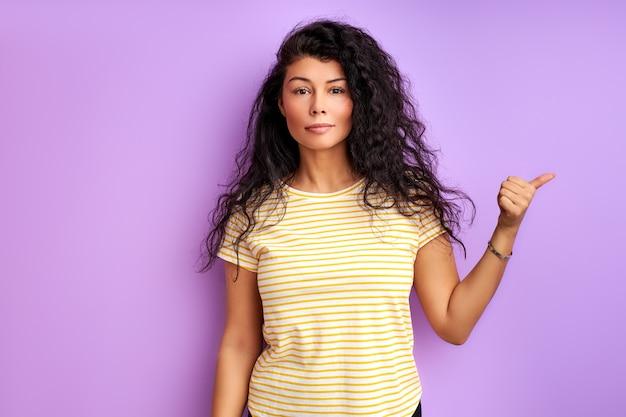 측면, 인덱스에서 성인 여자 가리키는 손가락. 광고용 사진. 격리 된 보라색 벽