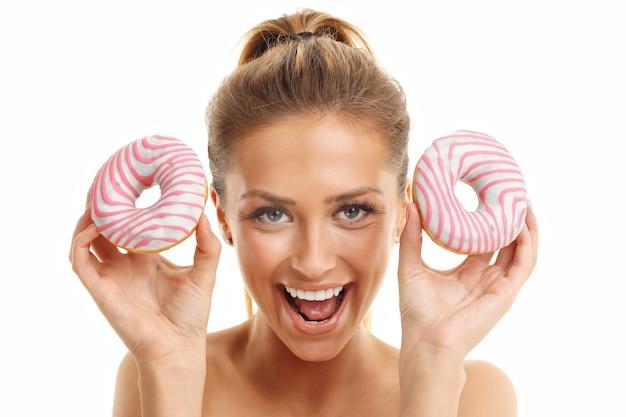 白い背景の上のドーナツでポーズをとって大人の女性