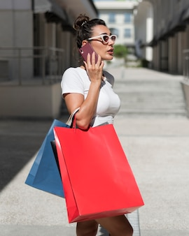 Adult woman posing with shopping bags