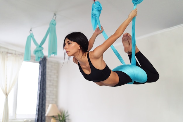 Adult woman practices anti-gravity yoga