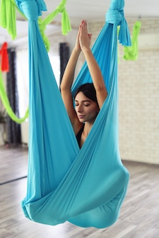 Adult woman practices anti-gravity yoga