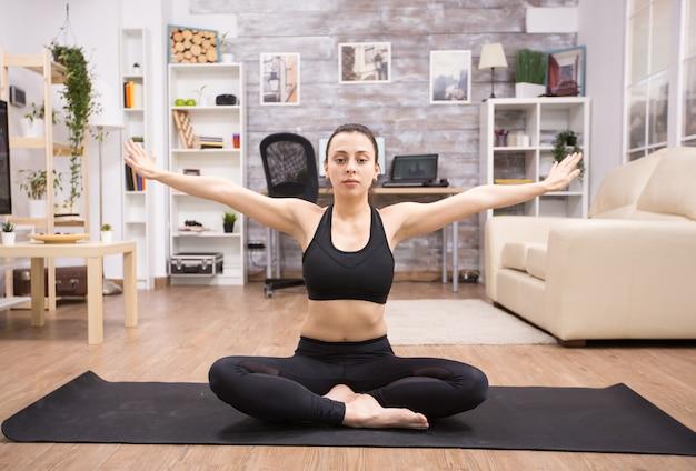 Donna adulta che pratica rilassamento seduto nella posa del loto yoga nel soggiorno.
