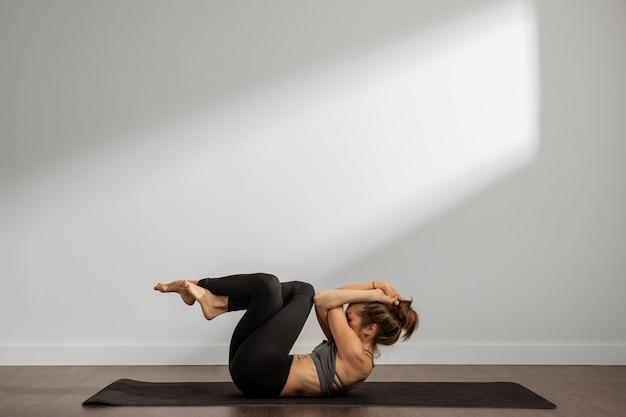 Взрослая женщина, практикующая йогу дома