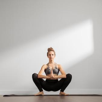 Donna adulta a praticare yoga a casa