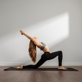Adult woman practicing yoga at home