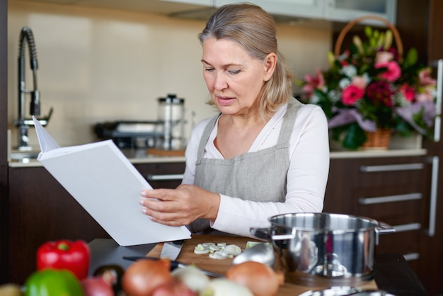Adult woman preparing food in kitchen and looking at recipe book