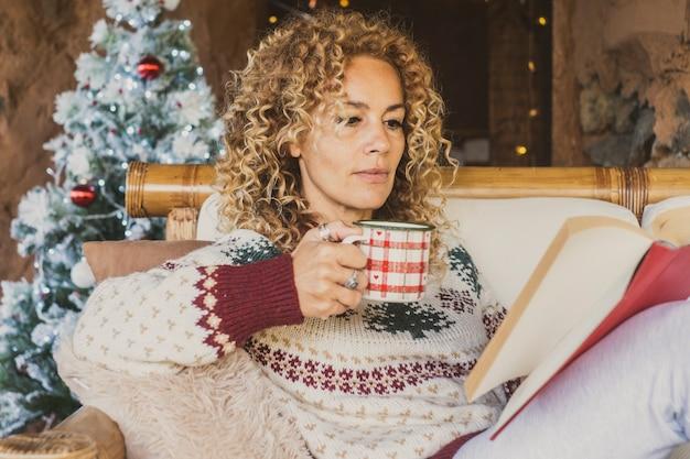 自宅でクリスマス休暇中に本を読んでいる大人の女性