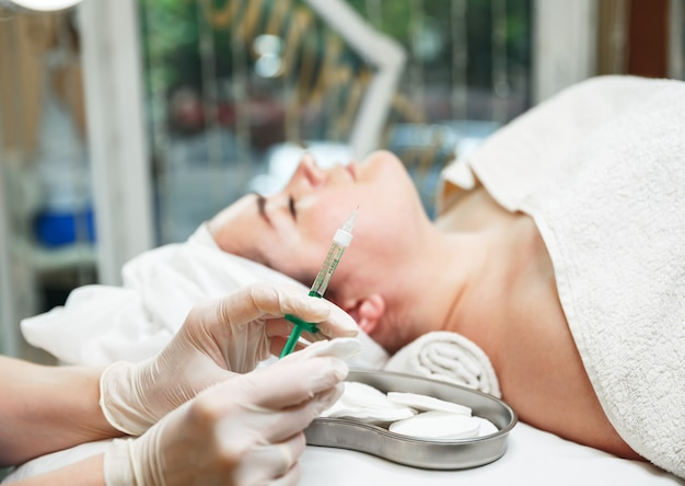 Adult woman receiving hyaluronic acid injection in a surgical clinic