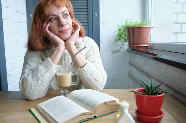 熱い飲み物のマグカップとキッチンで本を持って家でリラックスする大人の女性