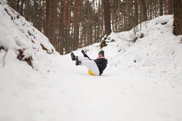大人の女性が急な山からそりの氷に乗る。冬の楽しみ。あらゆる目的のために。