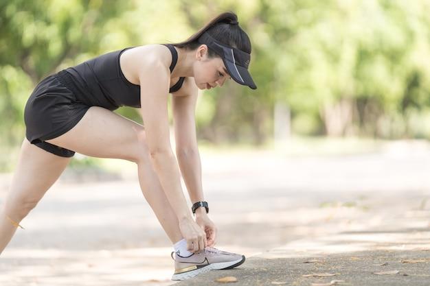 도시 공원에서 조깅 운동에 신발끈을 묶는 성인 여성 주자