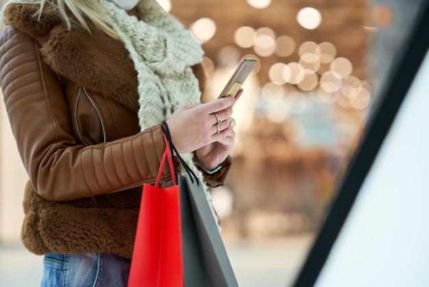 마스크, 코로나 바이러스 개념을 입고 스마트 폰을 사용하여 쇼핑몰에서 쇼핑하는 성인 여성