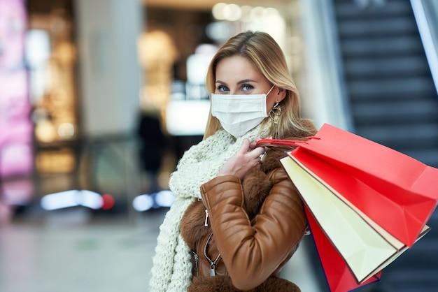 마스크, 코로나 바이러스 개념을 입고 쇼핑몰에서 쇼핑하는 성인 여성