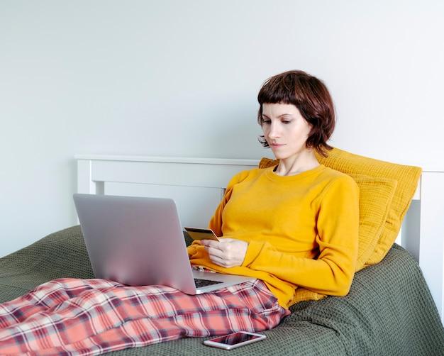 Взрослая женщина, делающая покупки в интернете с помощью кредитной карты
