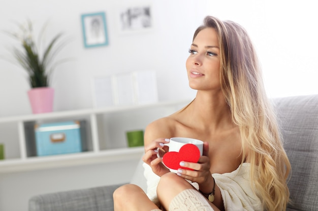 Взрослая женщина сидит на диване с кофе