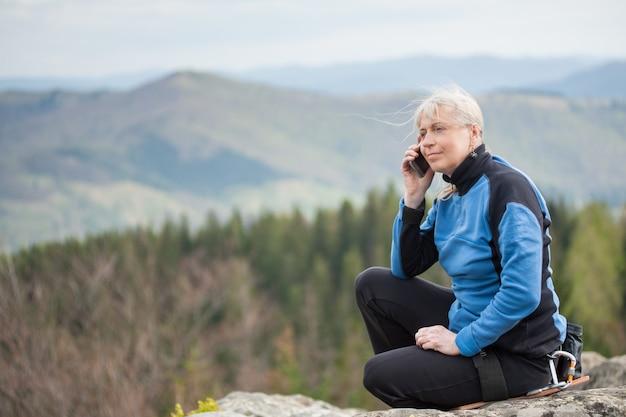 Adult woman sitting on the peak of rock
