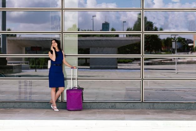 스마트폰을 사용하여 여행하는 동안 수하물을 들고 공항에 서 있는 성인 여성. 큰 창 배경