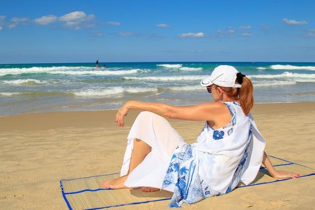 Взрослая женщина смотрела вдаль на пляже.