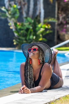 Adult woman in swimsuit lying on front on the edge of the pool looking up. african american woman with hat and sunglasses enjoying a summer day.
