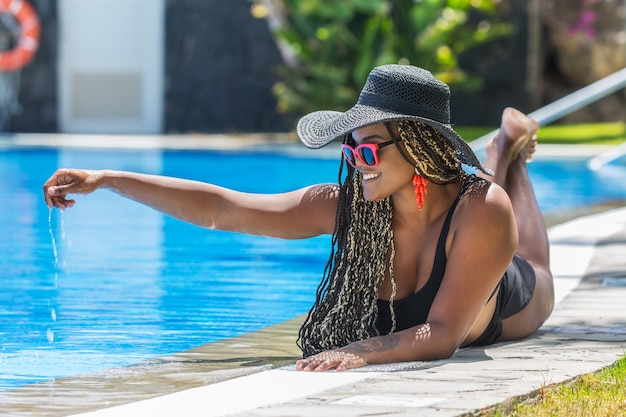 Adult woman in swimsuit lying on front on the edge of the pool touching the pool water. african american woman with hat and sunglasses enjoying a summer day.
