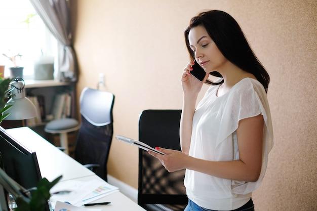 Взрослая женщина разговаривает по телефону в офисе