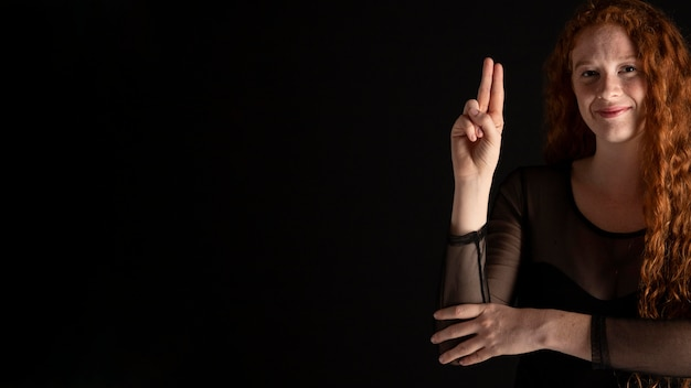 Adult woman teaching sign language with copy space