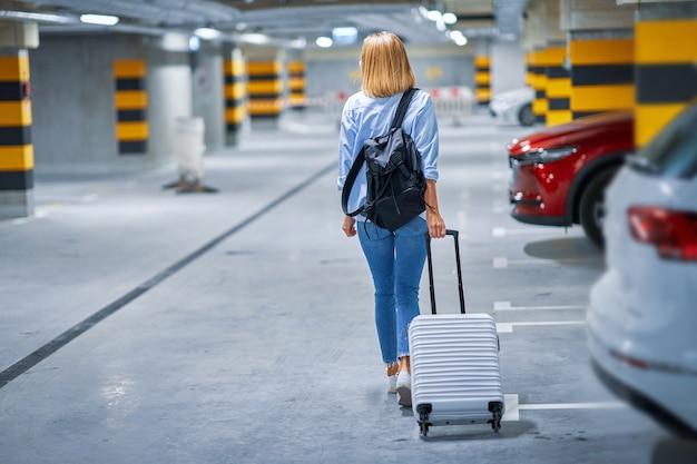 Взрослая женщина-турист на подземной стоянке аэропорта