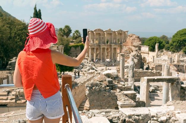 Взрослая женщина турист принимая фото с телефоном. счастливая женщина путешествует в солнечный летний день в эфесе, турция.