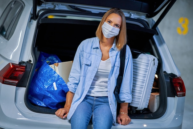 Взрослая женщина туристка в маске из-за процедур covid-19 на подземной стоянке аэропорта
