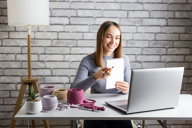 Adult woman transfering her knowledge of knitting in online classes
