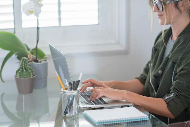 Взрослая женщина типа на портативном компьютере и улыбка счастлива за умную работу, бесплатный офис, домашнюю деятельность