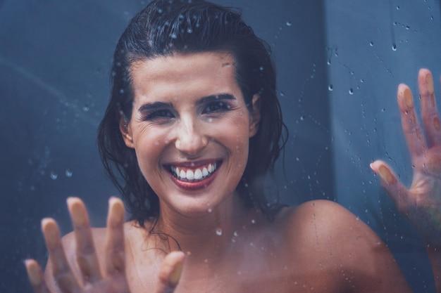 Взрослая женщина под душем в ванной комнате