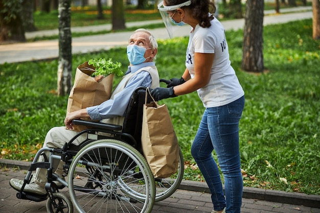 Adult woman walking with elderly man in the park