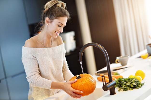 Adult woman washing pumpkin in the kitchen for halloween