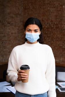 사무실에서 얼굴 마스크를 쓰고 성인 여성
