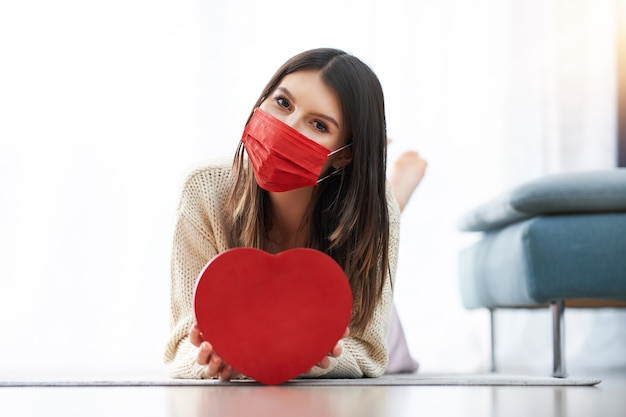 自宅で心を保持しているマスクを身に着けている大人の女性、バレンタインの概念