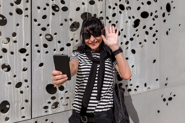 Adult woman wearing sunglasses waving at camera while videoconferencing outdoors