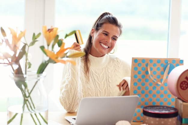 Adult woman wearing warm sweater and shopping online in christmas time