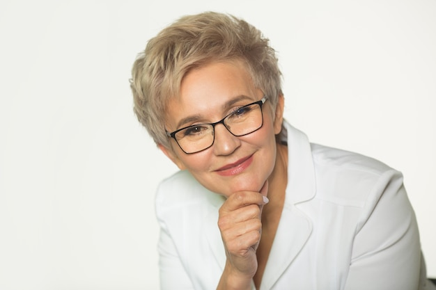 Взрослая женщина с короткой стрижкой в очках в белом пиджаке