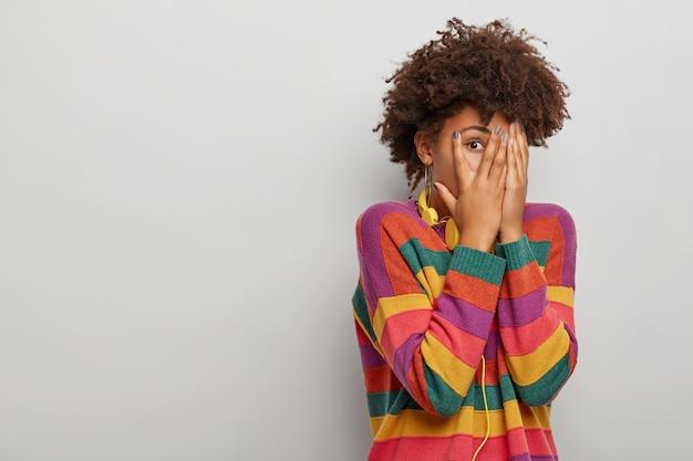 아프로 헤어 스타일을 가진 성인 여성은 손가락을 통해 보이고 양손으로 얼굴을 덮고 헤드폰과 줄무늬 스웨터를 입고 흰색 스튜디오 배경에 서 있습니다.