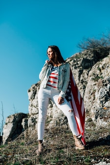 Adult woman with american flag in nature