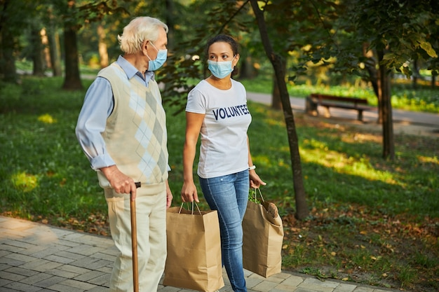 Adult woman with attractive old man walking through the park or wood