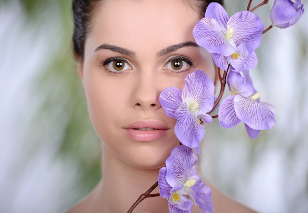 Adult woman with beautiful face and purple flowers.