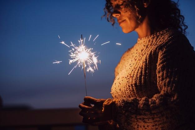 背景に青い空と夜に線香花火を保持している目を閉じて大人の女性