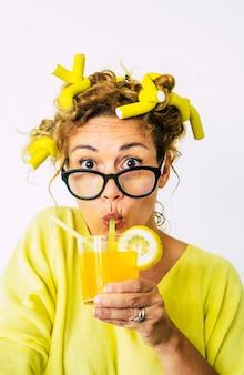 髪とオレンジジュースにカーラーを持つ大人の女性