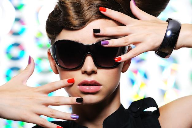 ファッション色とりどりのマニキュアと女性のスタイリッシュなサングラスを持つ大人の女性-クローズアップ