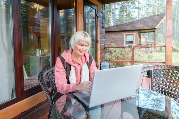 Взрослая женщина с ноутбуком на живописной террасе