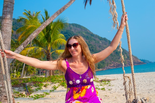 긴 금발 머리가 태국의 코창 섬에서 바다로 스윙 스윙하는 성인 여성