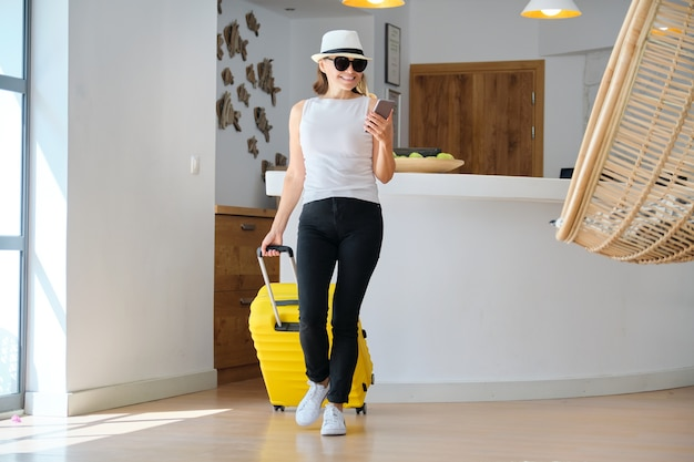 Adult woman with luggage with suitcase going to the hotel lobby